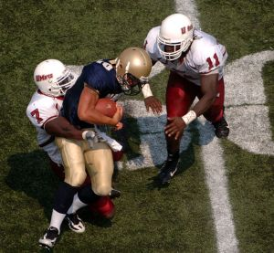 A tackle in a college football game between the Naval Academy and the University of Massachusetts
