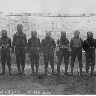 Gas mask-wearing British soldiers in front of a soccer goal in 1916