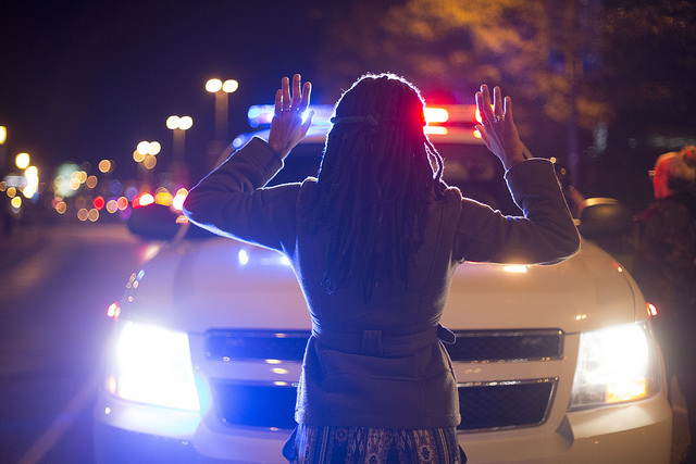 Woman holding her hands up in front of a police car at a Ferguson protest