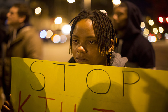 "Photo of woman in Ferguson holding a ""Stop Killing"" poster on Nov. 25th"