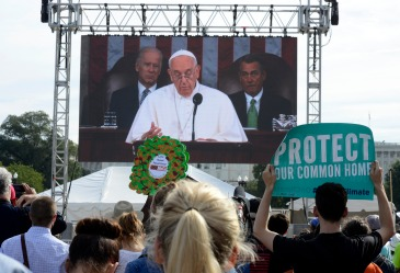 Environmental activists watch the Pope address Congress