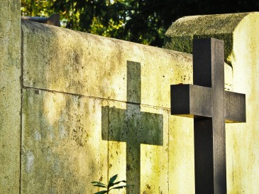 Image of a cross casting a shadow on a grave