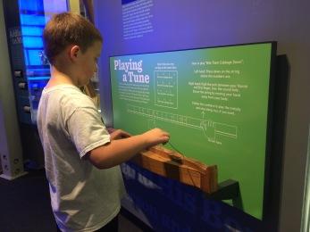 Isaiah playing a primitive dulcimer