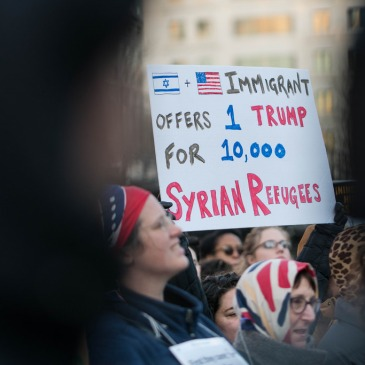 """Protestor holding a sign, """"Immigrant offers 1 Trump for 10,000 Syrian Refugees"""""""