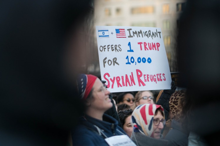 "Protestor holding a sign, ""Immigrant offers 1 Trump for 10,000 Syrian Refugees"""