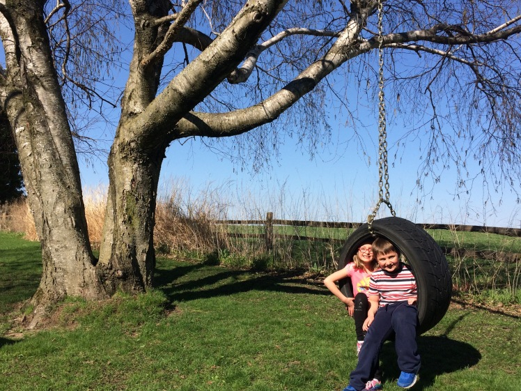 Lena and Isaiah in a tire swing on the family farm