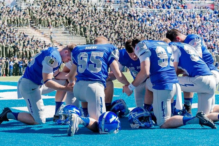 Air Force football player praying